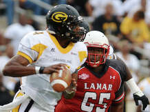 Lamar's Omar Tebo, No. 65, moves in on Grambling State quarterback D.J. Williams during Saturday's game. The Lamar Cardinals opened their season Saturday evening against the Grambling State Tigers at Provost Umphrey Stadium. Photo taken Saturday 8/30/14 Jake Daniels/@JakeD_in_SETX