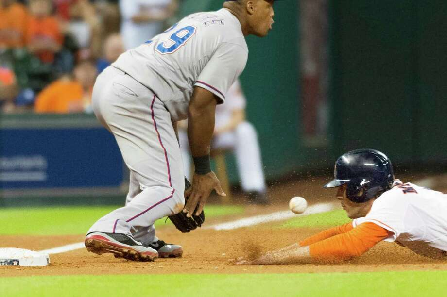 Astros right fielder Jake Marisnick beats the throw to Rangers third baseman Adrian Beltre as he advances on a fly ball by Matt Dominguez during the seventh inning. Photo: Smiley N. Pool, Houston Chronicle / © 2014  Smiley N. Pool