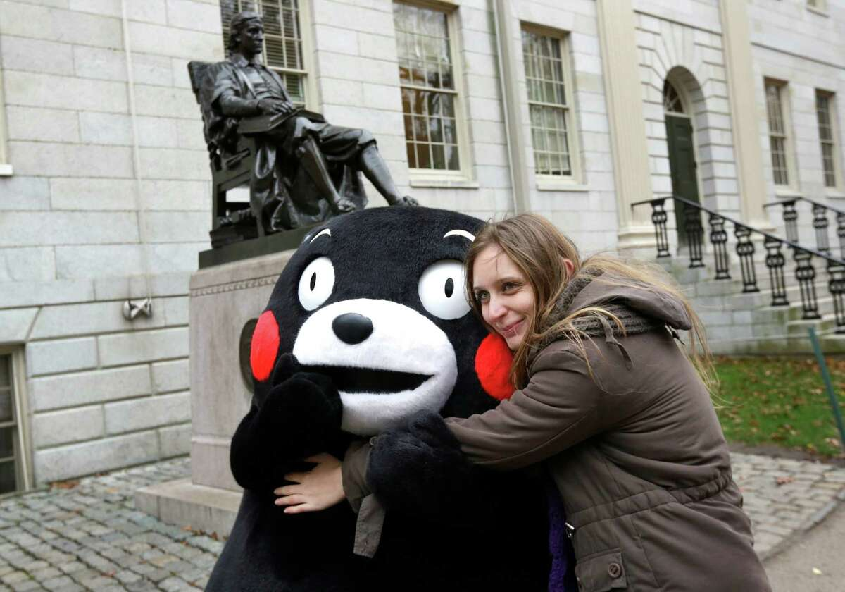 FILE - In this Nov. 12, 2013, Kumamon, left, a popular black bear character from Japan, is hugged by Mariel Cerra, of Buenos Aires, Argentina, in front of a statue of John Harvard on the campus of Harvard University in Cambridge, Mass., as the Kumamon character that originated in Japan's Kumamoto prefecture, or state, visited the university and Fenway Park in Boston on the day. Characters are not just for kids in Japan, but a part of business and social life. Goofy black bear Kumamon is perhaps the most successful of the mushrooming new characters that seek to promote a locality in Japan.