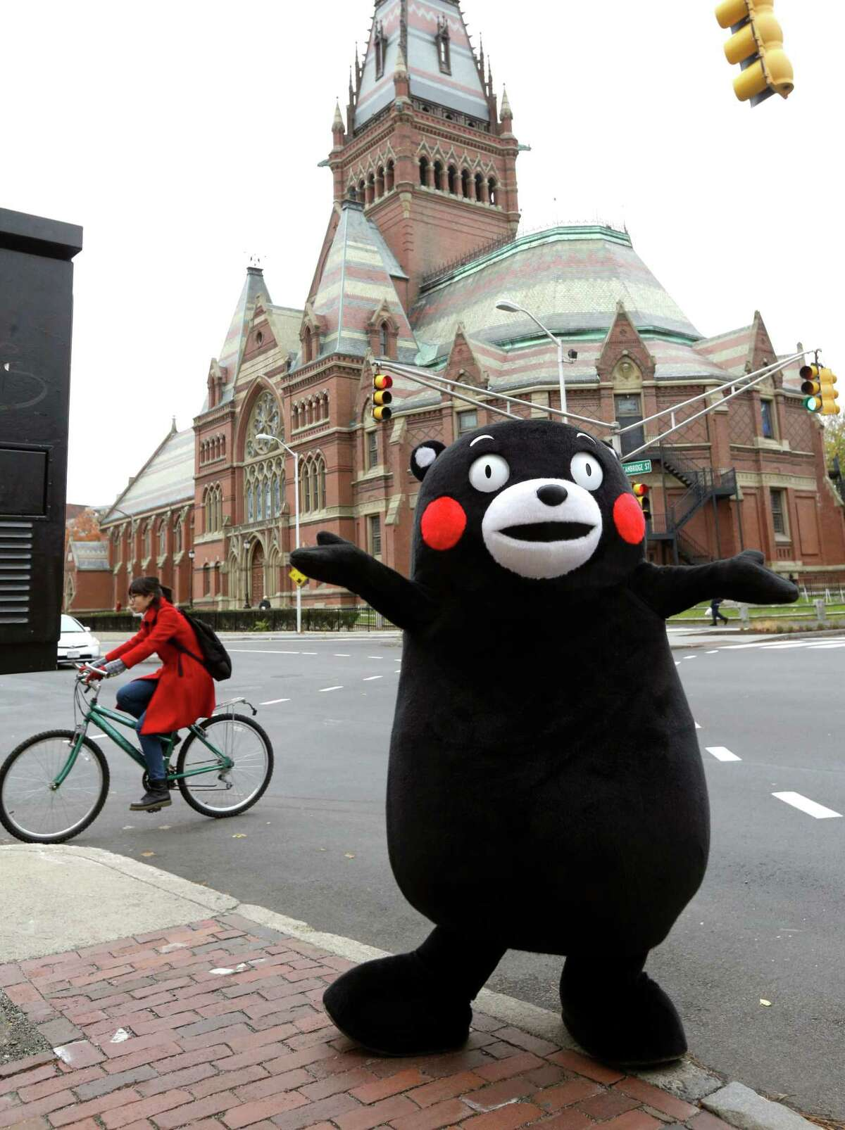 FILE - In this Nov. 12, 2013 file photo, Kumamon, a popular black bear character from Japan, dances on the street outside Harvard University in Cambridge, Mass. when the Kumamon character that originated in Japan's Kumamoto prefecture, or state, visited the university and Fenway Park in Boston on the day. Characters are not just for kids in Japan, but a part of business and social life. Goofy black bear Kumamon is perhaps the most successful of the mushrooming new characters that seek to promote a locality in Japan.