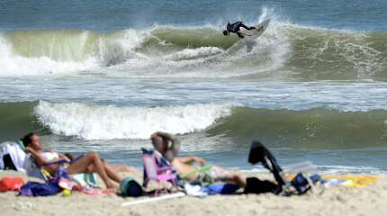 Surfers take advantage of early swells from a tropical storm on the beach off 6th Street in Ship Bottom, on Long Beach Island, N.J. Thursday, Aug. 28, 2014. Forecasters are warning of rip currents at the Jersey Shore.