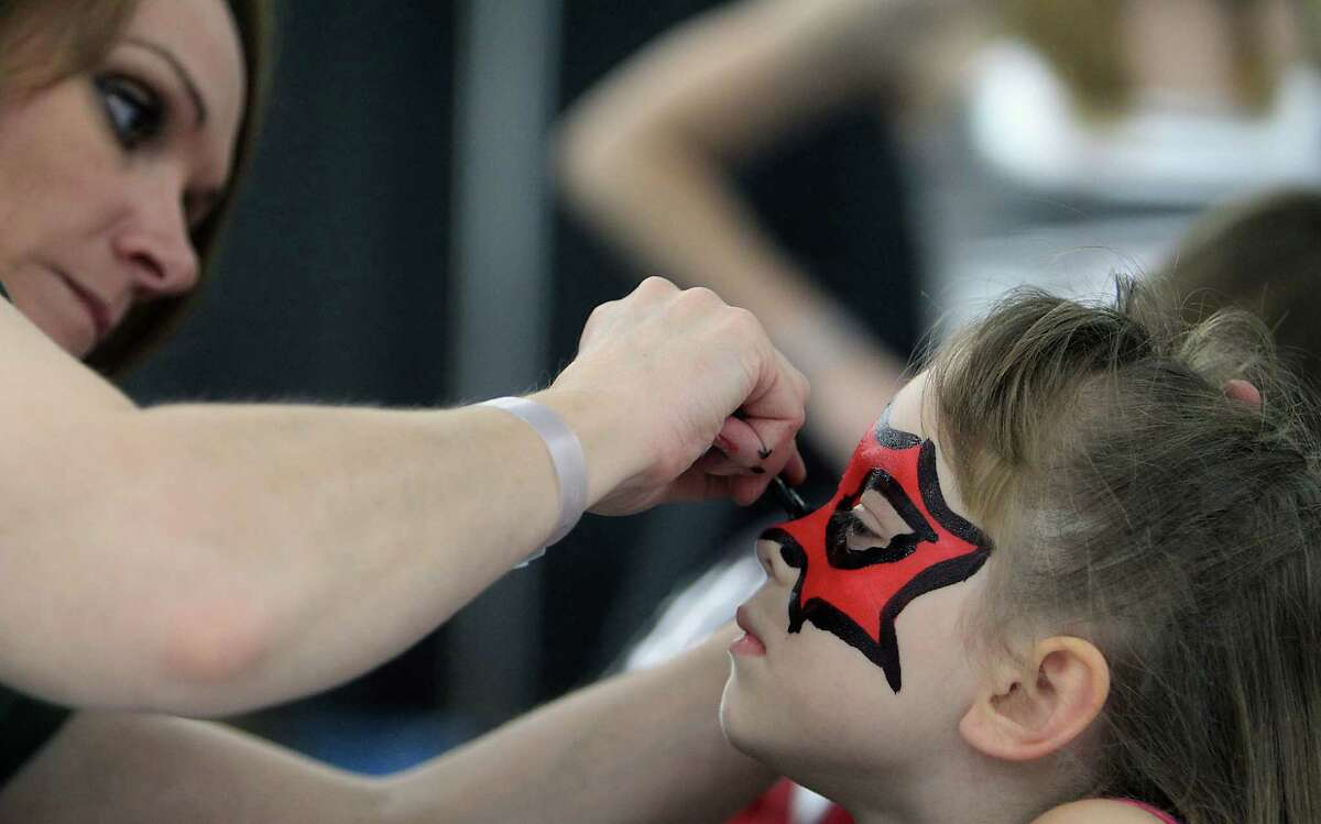 Jill Caldwell left, paints six-year-old Juliana Walker's face during the Amazing Houston Comic Con convention at George R Brown Convention Center Sunday, Aug. 31, 2014, in Houston.