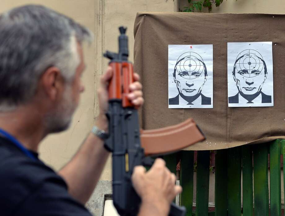 "A man prepares to shoot at targets depicting a portrait of Russian President Vladimir Putin, in a shooting range in the center of the western Ukrainian city of Lviv, on August 31, 2014. Russian President Vladimir Putin called on August 31 for immediate talks on the future of war-torn east Ukraine, saying for the first time that ""statehood"" should be discussed. AFP PHOTO/ YURKO DYACHYSHYNYURIY DYACHYSHYN/AFP/Getty Images Photo: Yuriy Dyachyshyn, AFP/Getty Images"