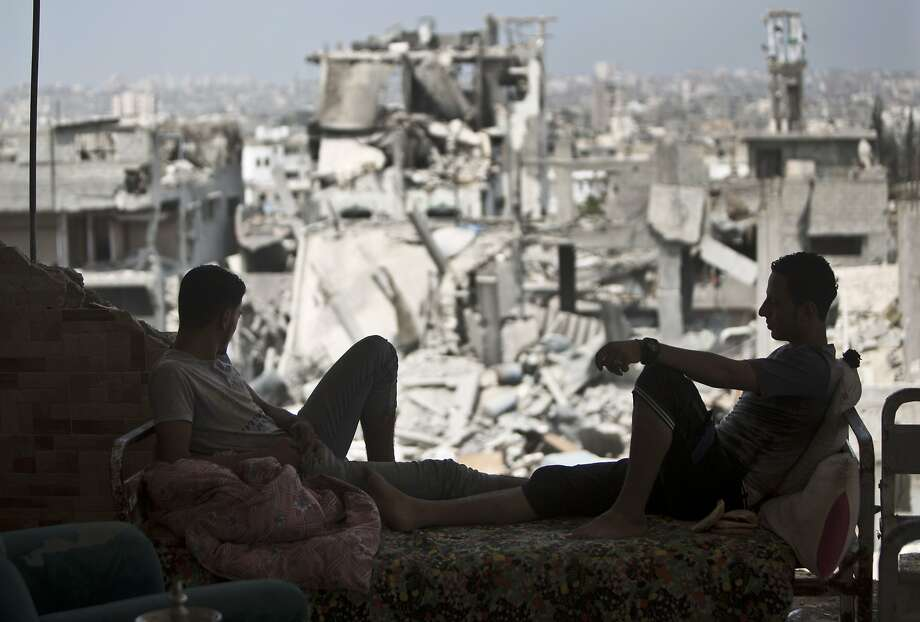 Palestinians sit in their destroyed house after returning to eastern Gaza City during the cease-fire. Photo: Mahmud Hams, AFP/Getty Images