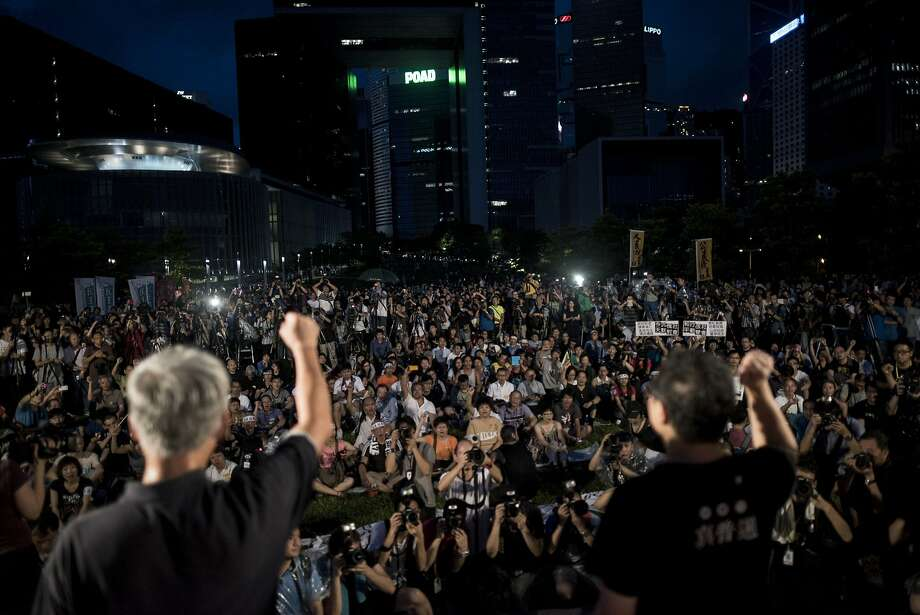 TOPSHOTS Benny Tai (R), co-founder of the Occupy Central movement, rallies with democracy activists next to the Hong Kong government complex on August 31, 2014. China insisted on August 31 that candidates for Hong Kong's next leader must be screened in advance, triggering tears and fury in the city, where democracy activists vowed to press ahead with a planned takeover of the financial district.   AFP PHOTO / ALEX OGLEAlex Ogle/AFP/Getty Images Photo: Alex Ogle, AFP/Getty Images