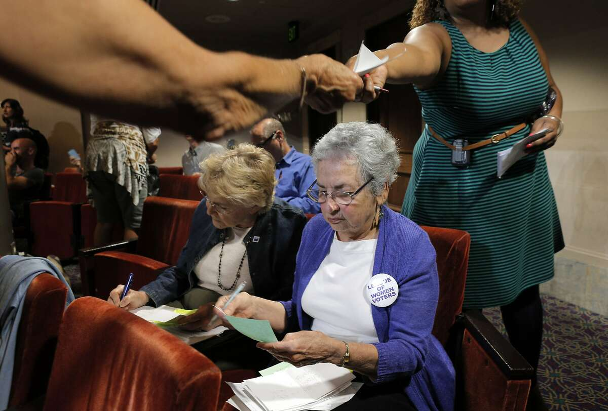 Mary Bergan left, and Rachel Kahn-Hut, right, with the League of Women Voters, collect questions from the audience for the candidates for mayor of Oakland at the Oakland Mayoral Candidate Forum at City Hall in Oakland, Calif., on Thursday, August 21, 2104.