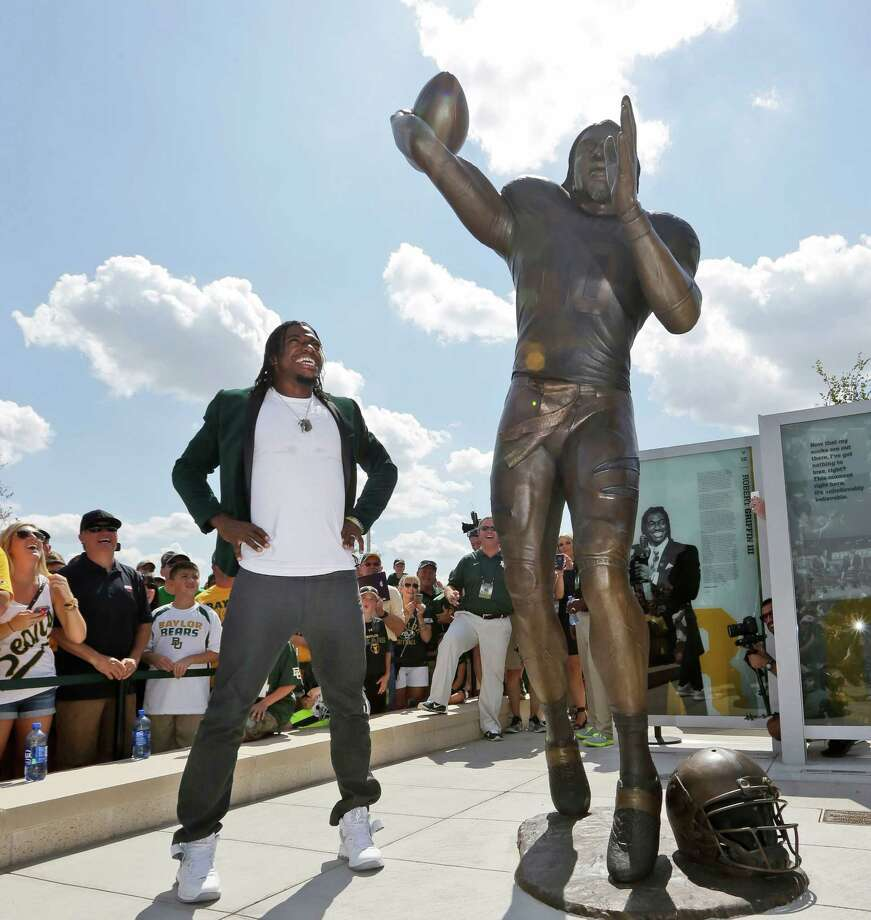 Washington Redskins quarterback Robert Griffin III looks at a bronze statute of himself after it was unveiled outside the new McLane Stadium before an NCAA college football game between SMU and Baylor Sunday, Aug. 31, 2014, in Waco, Texas. Griffin won the Heisman Trophy when he played at Baylor. (AP Photo/LM Otero) Photo: LM Otero, Associated Press / AP