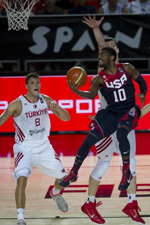U.S. guard Kyrie Irving, who scored 13 points, drives to the basket in front of Turkey's Baris Hersek (left) in the Americans' victory in Spain. Photo: Alvaro Barrientos, Associated Press