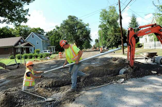Electricians Kim Macri, left, and Chris Prior of Stilsing Electric run a conduit for a new traffic light and pedestrian poles on Sand Creek Road near Wilkins Avenue on Thursday, Aug. 28, 2014, in Colonie N.Y. (Cindy Schultz / Times Union) Photo: Cindy Schultz / 00028392A