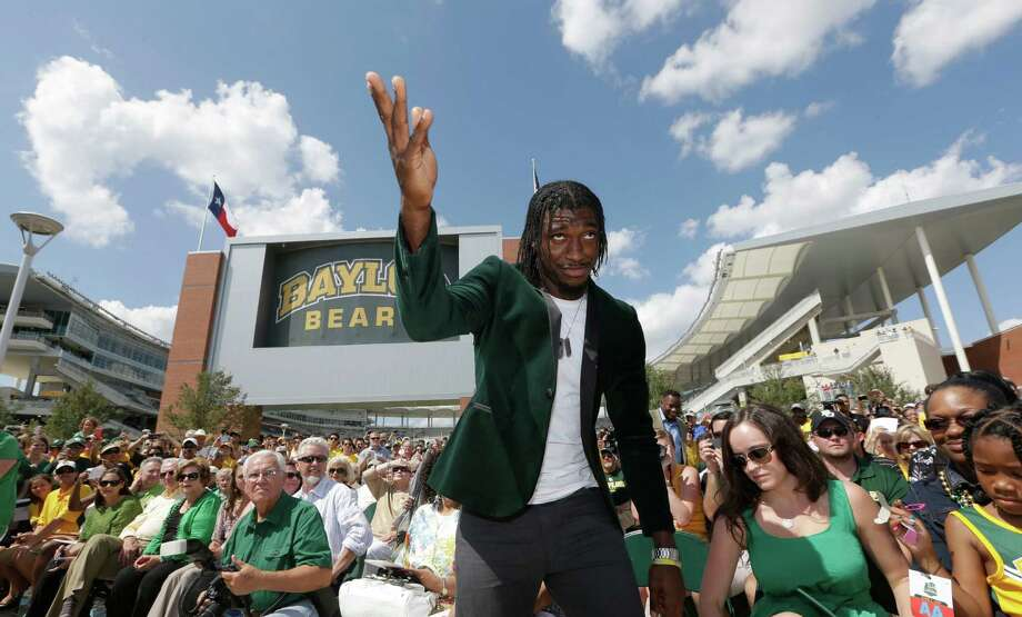 Washington Redskins quarterback Robert Griffin III acknowledges fans as he heads to unveil a bronze statute of himself outside the new McLane Stadium before an NCAA college football game between SMU and Baylor Sunday, Aug. 31, 2014, in Waco, Texas. Griffin won the Heisman Trophy when he played at Baylor. (AP Photo/LM Otero) Photo: LM Otero, Associated Press / AP