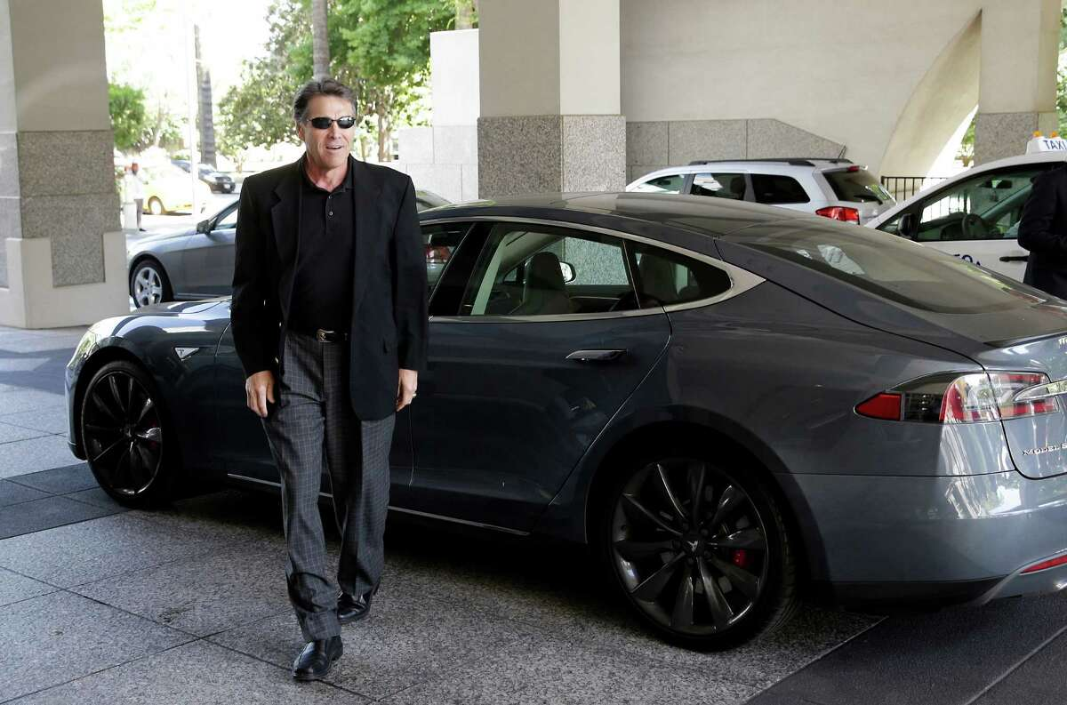 Gov. Rick Perry walks over to talk to reporters after driving up in a Tesla Motors Type S electric car in Sacramento. Texas and California are among states where Tesla may build a $5 billion factory to make batteries for a new model of car.