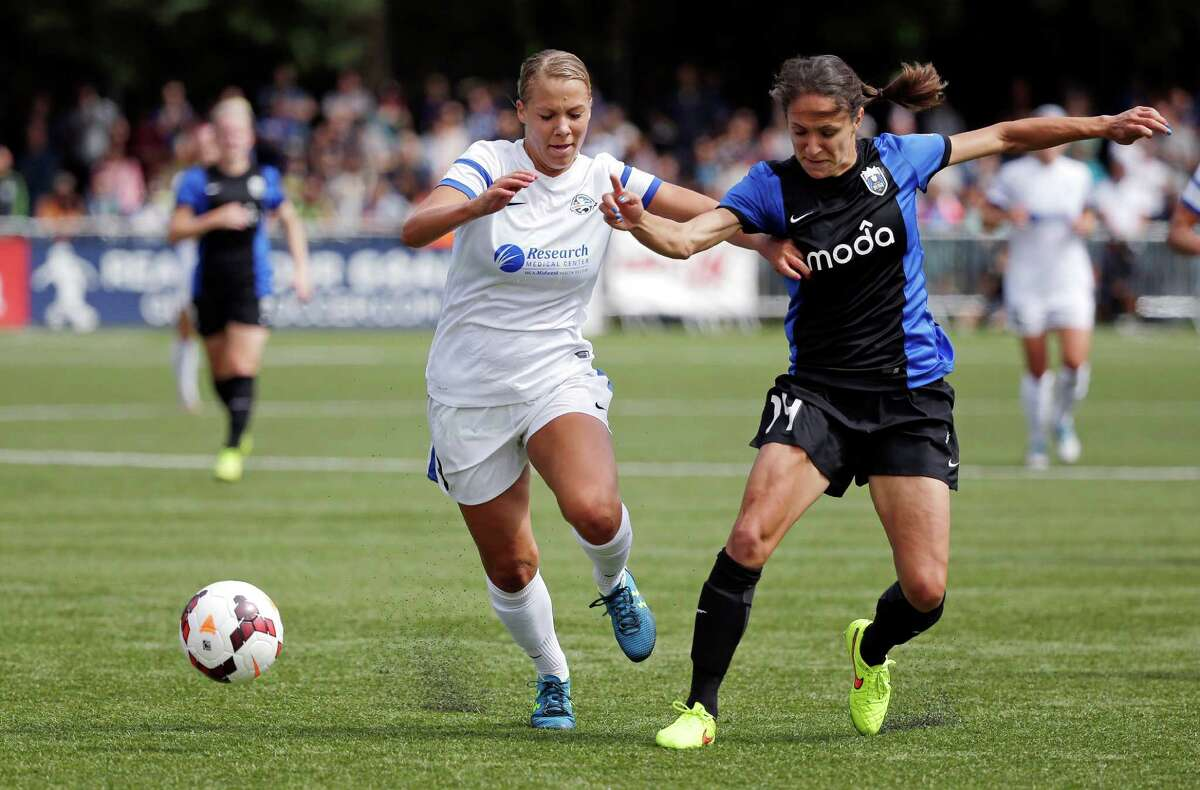 FC Kansas City's Merritt Mathias, left, and Seattle Reign FC's Stephanie Cox fight for the ball in the second half of the NWSL championship soccer match Sunday, Aug. 31, 2014, in Tukwila, Wash. Kansas City won 2-1.