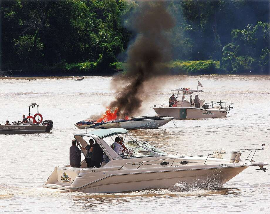 A pleasure boat, foreground, passes a boat on fire Sunday, Aug. 31, 2014, in the middle of the Mississippi River about one half mile east of Grafton, Ill., as boats from Grafton's QEM Fire Protection District, left, and the Illinois Conservation Police, right, surround the burning craft. QEM fire officials said the occupants were able to safely transfer to a nearby pontoon boat when the fire erupted. QEM made two attempts to pull the boat close to the shore. Dozens of boaters watched as did hundreds of slowing motorists on the Great River Road despite the efforts of Jersey County, Ill., Sheriff's Deputies to keep the traffic moving. (AP Photo/The Telegraph, John Badman) Photo: John Badman, Associated Press