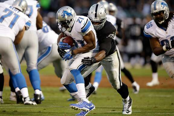 OAKLAND, CA - AUGUST 15:  Reggie Bush #21 of the Detroit Lions gets hit by Justin Tuck #91 of the Oakland Raiders during their preseason game at O.co Coliseum on August 15, 2014 in Oakland, California.  (Photo by Ezra Shaw/Getty Images)