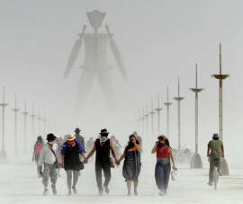 Burning Man participants walk through dust last year.