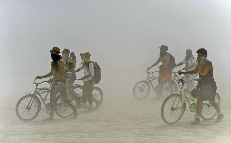 Burning Man participants walk their bikes during a dust storm at the annual Burning Man event on the Black Rock Desert of Gerlach, Nev., on Friday, Aug. 29, 2014. Organizers call Burning Man the largest outdoor arts festival in North America, with its drum circles, decorated art cars, guerrilla theatrics and colorful theme camps. (AP Photo/The Reno Gazette-Journal, Andy Barron) Photo: Andy Barron, Associated Press
