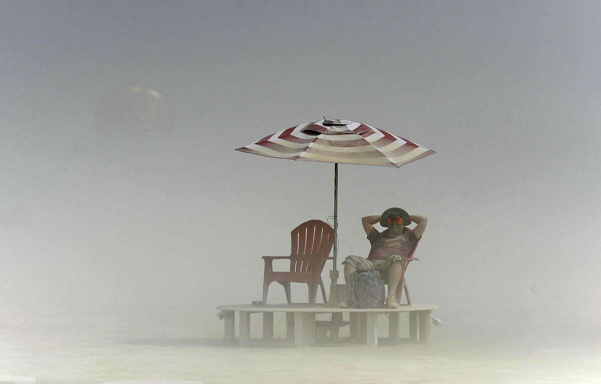 A Burning Man participant relaxes on the playa during a dust storm on the Black Rock Desert of Gerlach, Nev., on Friday, Aug. 29, 2014. Organizers call Burning Man the largest outdoor arts festival in North America, with its drum circles, decorated art cars, guerrilla theatrics and colorful theme camps.