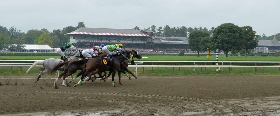 Horses leave the gate at the at the 6 1/2  furlong start in the third race on the card on a rainy Su