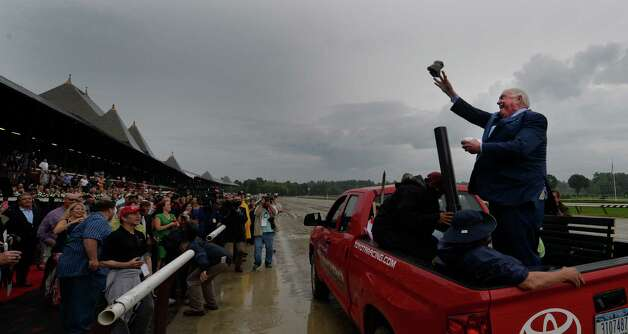 Track announcer Tom Durkin throws t-shirts from a pickup truck as he exits the track at the end of his retirement party Sunday afternoon Aug. 31, 2014  at the Saratoga Race Course in Saratoga Springs, N.Y.     (Skip Dickstein/Times Union) Photo: SKIP DICKSTEIN