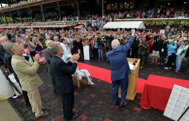 Track announcer Tom Durkin, center, is given a retirement party in the winner's circle Sunday afternoon Aug. 31, 2014  at the Saratoga Race Course in Saratoga Springs, N.Y.     (Skip Dickstein/Times Union) Photo: SKIP DICKSTEIN