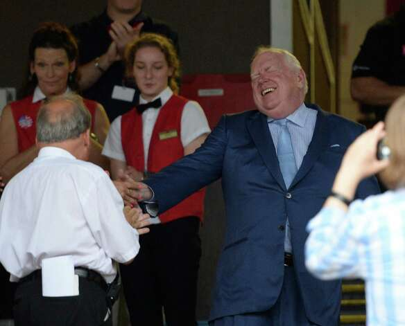 Track announcer Tom Durkin, center, is greeted by well-wishers in the crowd before a retirement party in the winner's circle Sunday afternoon Aug. 31, 2014  at the Saratoga Race Course in Saratoga Springs, N.Y.     (Skip Dickstein/Times Union) Photo: SKIP DICKSTEIN