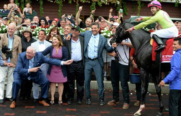 Track announcer Tom Durkin, left, hams is up after calling his final race and joins the crowd in the winner's circle Sunday afternoon Aug. 31, 2014  at the Saratoga Race Course in Saratoga Springs, N.Y.   The winning horse was Condo Commando ridden by jockey Joe Bravo who is pointing at Durkin.  (Skip Dickstein/Times Union) Photo: SKIP DICKSTEIN