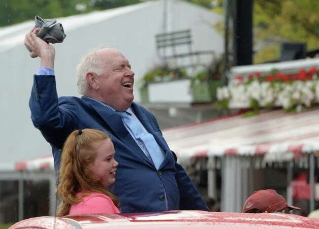 Track announcer Tom Durkin throws t-shirts as he exits the track after his retirement party in the winner's circle Sunday afternoon Aug. 31, 2014  at the Saratoga Race Course in Saratoga Springs, N.Y.     (Skip Dickstein/Times Union) Photo: SKIP DICKSTEIN
