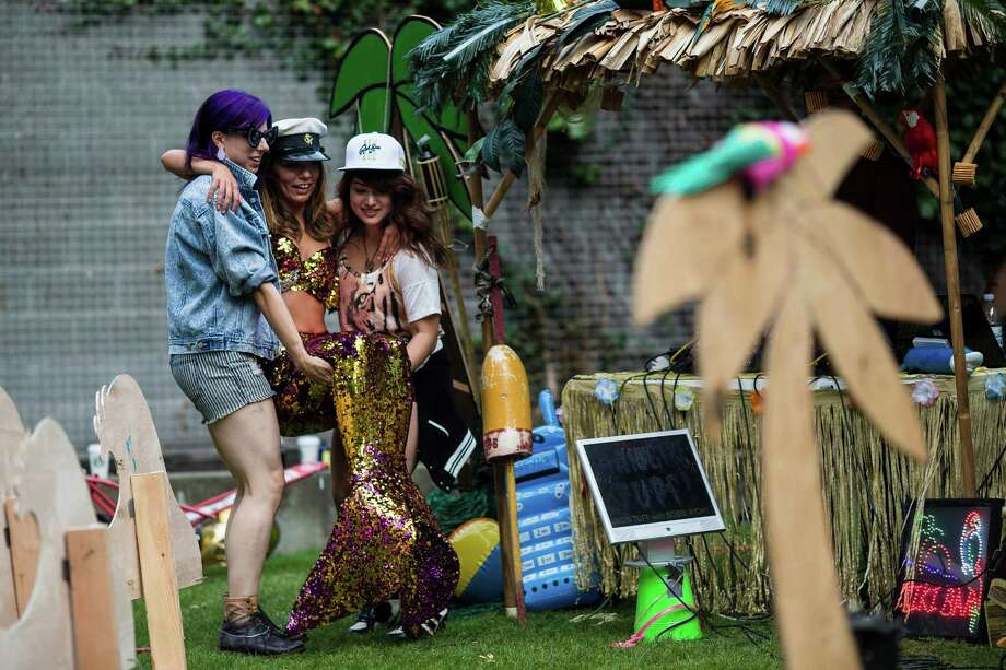 """Two women help """"the drunken mermaid"""" into her seat on the second day of Bumbershoot, Seattle's annual music and arts festival, photographed Sunday, August 31, 2014, in Seattle, Washington. Photo: JORDAN STEAD, SEATTLEPI.COM / SEATTLEPI.COM"""