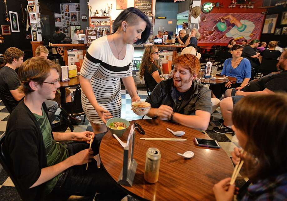 Victoria Walker serves up ramen bowls at the Logon Cafe on Thursday. Walker is offering tastings to help finance owning her own ramen restaurant. Photo taken Thursday, August 14, 2014 Guiseppe Barranco/@spotnewsshooter