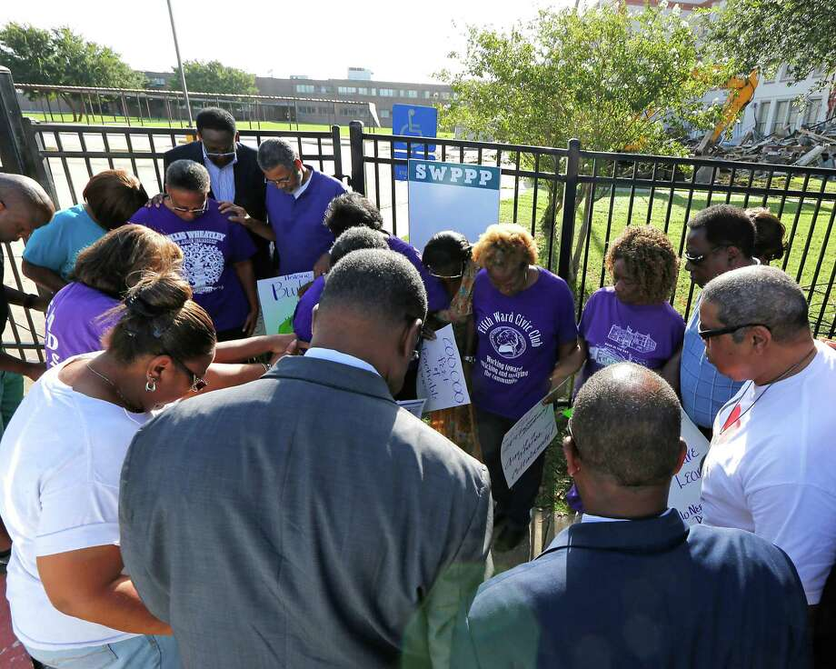 A prayer prior to community leaders protesting the demolition of the historic Wheatley / E. O. Smith school in the Fifth Ward Monday, Sept. 1, 2014, in Houston. Photo: James Nielsen, Houston Chronicle / © 2014  Houston Chronicle
