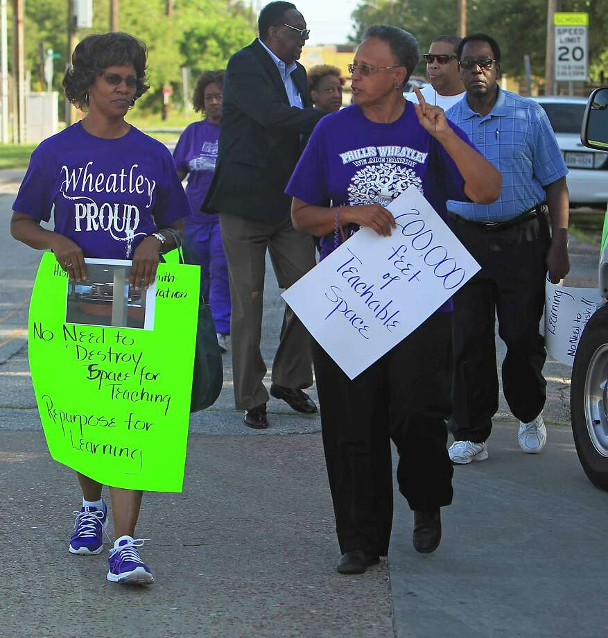 People carries signs as community leaders protest the demolition of the historic Wheatley / E. O. Smith school in the Fifth Ward Monday, Sept. 1, 2014, in Houston. Photo: James Nielsen, Houston Chronicle / © 2014  Houston Chronicle