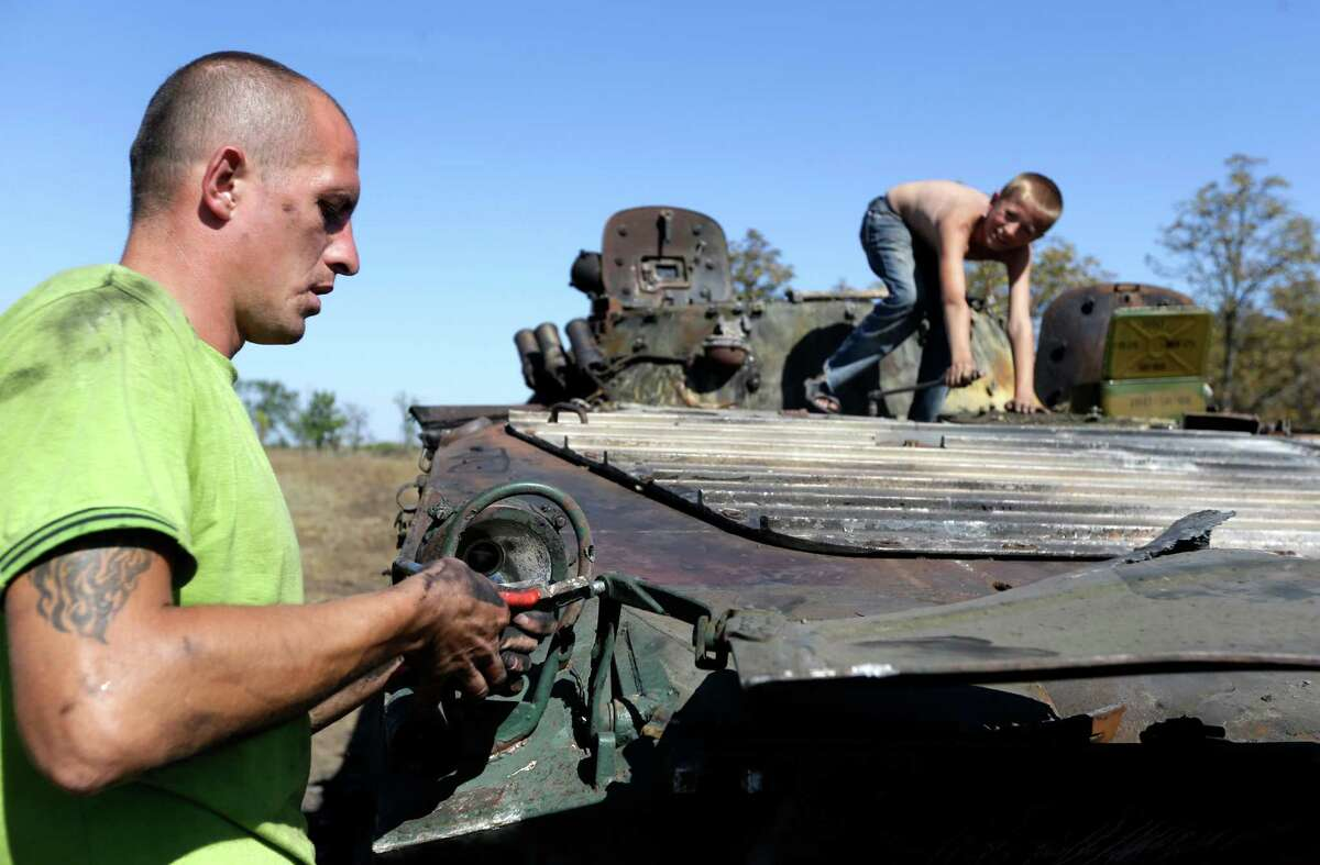 Alexander Bespalko, left, with his son Denis loosen parts from a burned-out Ukrainian armored personnel carrier in the village of Hrabske, eastern Ukraine, Sunday, Aug. 31, 2014. The fight for Ilovaisk and surrounding areas, including the village of Hrabske, between Ukrainian government troops and pro-Russian separatist fighters was bitter and lasted the best part of a month.