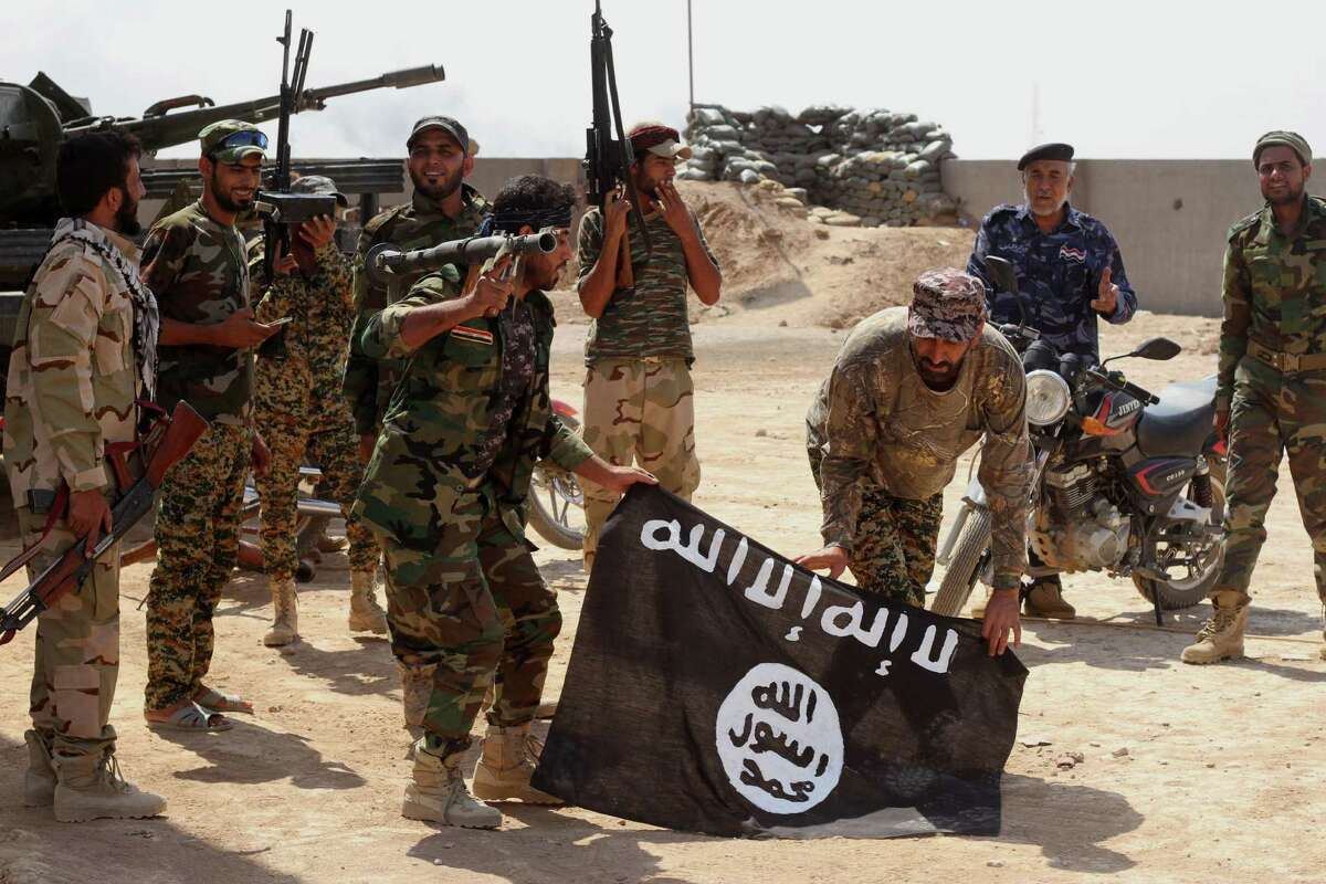 Iraqi security forces hold a flag of the Islamic State group they captured during an operation outside Amirli, some 105 miles (170 kilometers) north of Baghdad, Iraq, Monday, Sept. 1, 2014. Aid began flowing into the small northern Shiite town in Iraq on Monday, a day after security forces backed by Iran-allied Shiite militias and U.S. airstrikes broke a two-month siege by insurgents in a rare victory by government forces.
