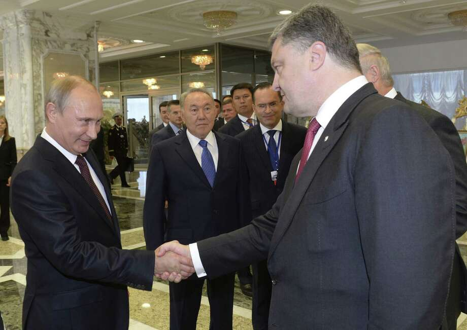 Russian President Vladimir Putin (left) shakes hands with Ukrainian President Petro Poroshenko in Minsk, Belarus, prior to a summit to discuss the crisis in Ukraine. Photo: Associated Press / POOL Kazakh Presidential Press S
