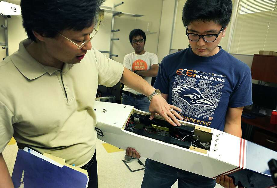 Danel Pack, left, Chair of Electrical and Computer Engineering Department at UTSA, points out the inner workings of a drone held by student Yonggun Lee. A grant from the Department of Defense will enable UTSA's drone researchers to acquire two state-of-the-art systems to analyze brain waves and applying that knowledge to control drones with brain waves. Wednesday, August. 27, 2014. Photo: San Antonio Express-News / © 2012 San Antonio Express-News