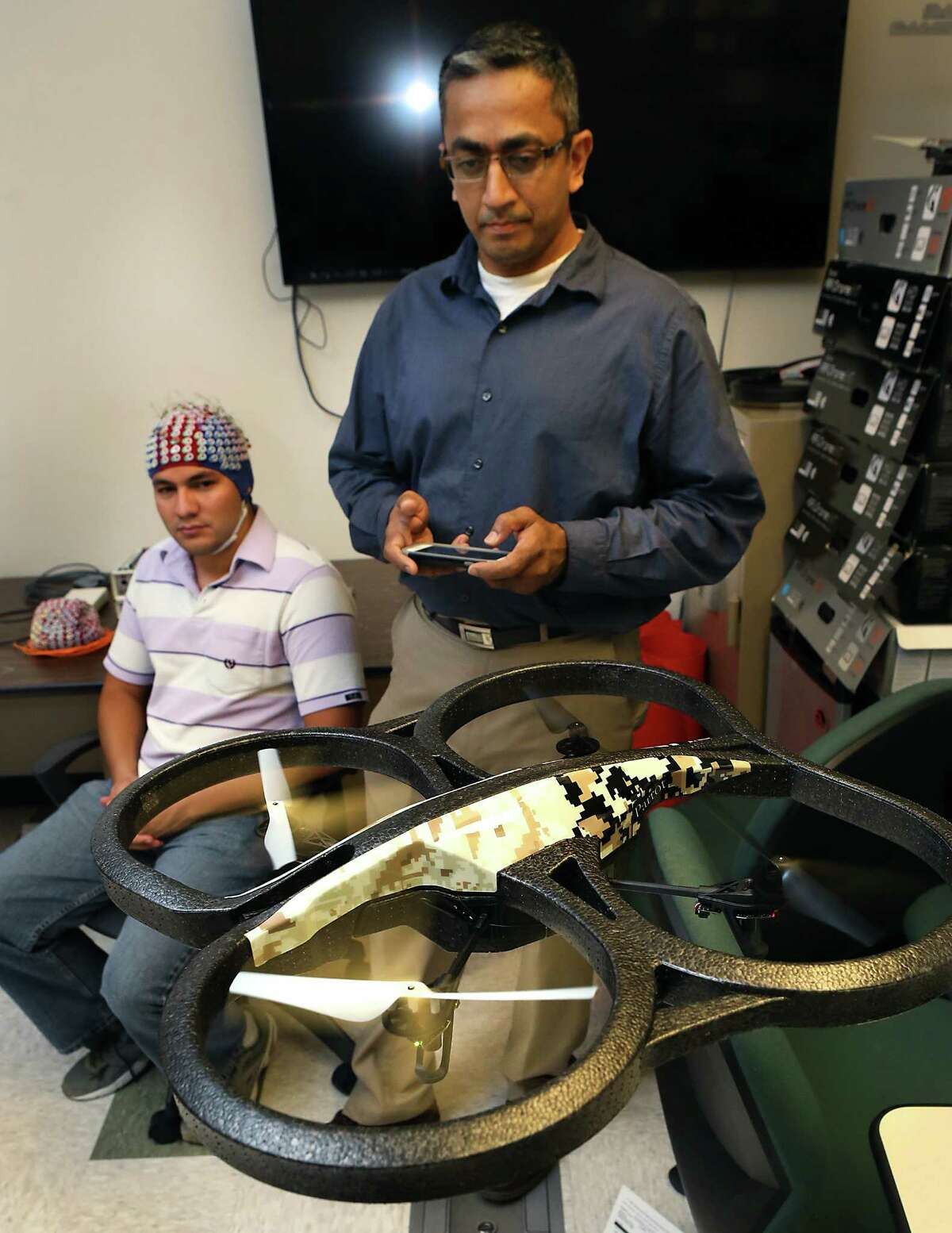Prasanna Kolar, right, a masters student in Computer Engineering at UTSA, controls a quad copter through an app on his smart phone. Kolar and other students at UTSA's Electrical and Computer Engineering Department are studying how to control a drone with brain waves collected by the electroencephalogram system (cap) worn by Mauricio Merino, left, a masters student in Electrical Engineering. A grant from the Department of Defense will enable UTSA's drone researchers to acquire two state-of-the-art systems to analyze brain waves and applying that knowledge to control drones with brain waves. Wednesday, August. 27, 2014.