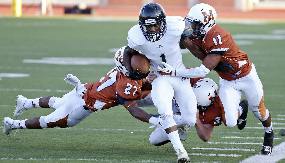 Steele's Jaylen Harris Bolts past Madison's Ajahn Forrester (from left), Patryck Banks and Isaiah Martin during first half action Saturday at Heroes Stadium. Steele blanked the Mavs, 35-0.
