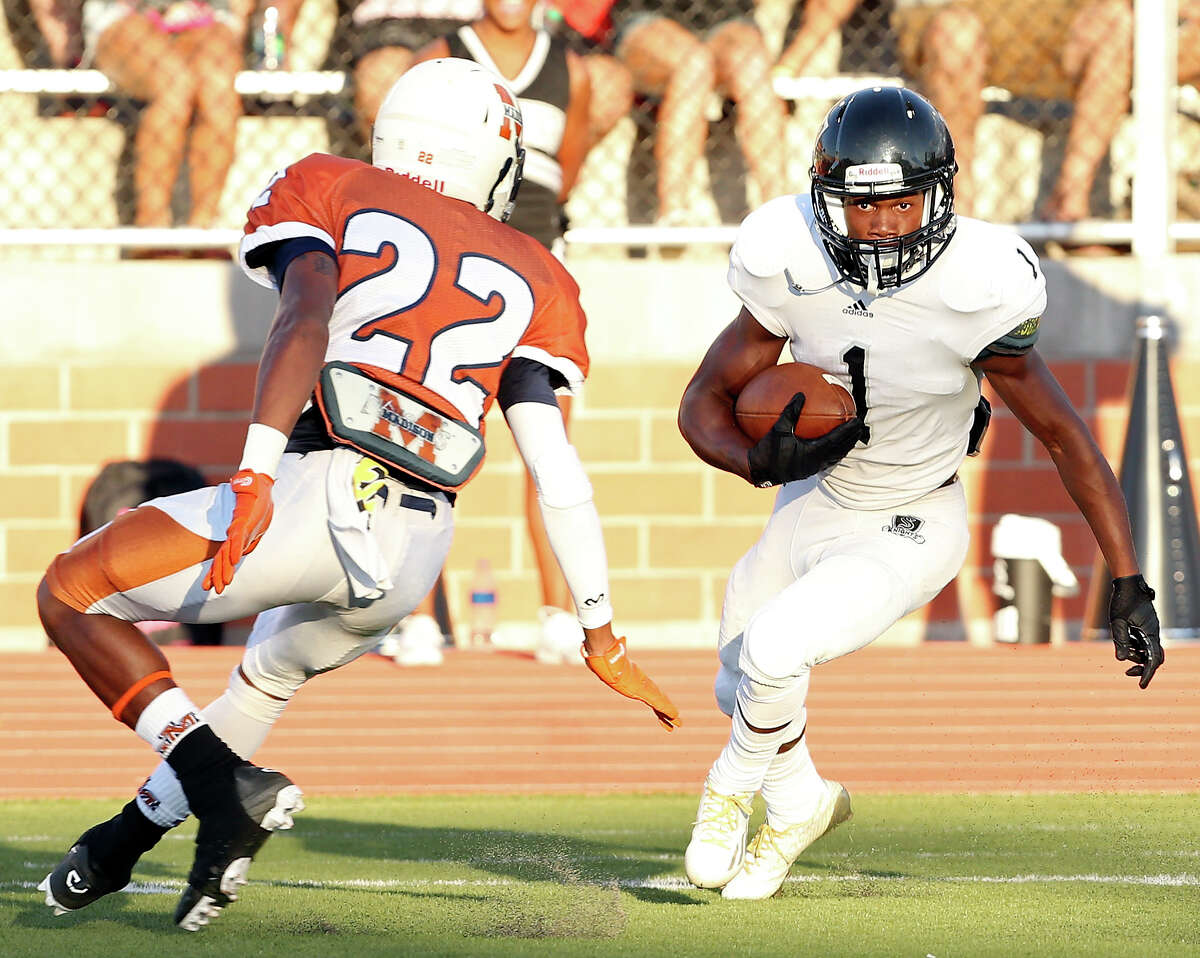 Steele's Jaylen Harris looks for room around Madison's DJ Johnson during first half action Saturday Aug. 30, 2014 at Heroes Stadium. Harris scored a touchdown on the play.