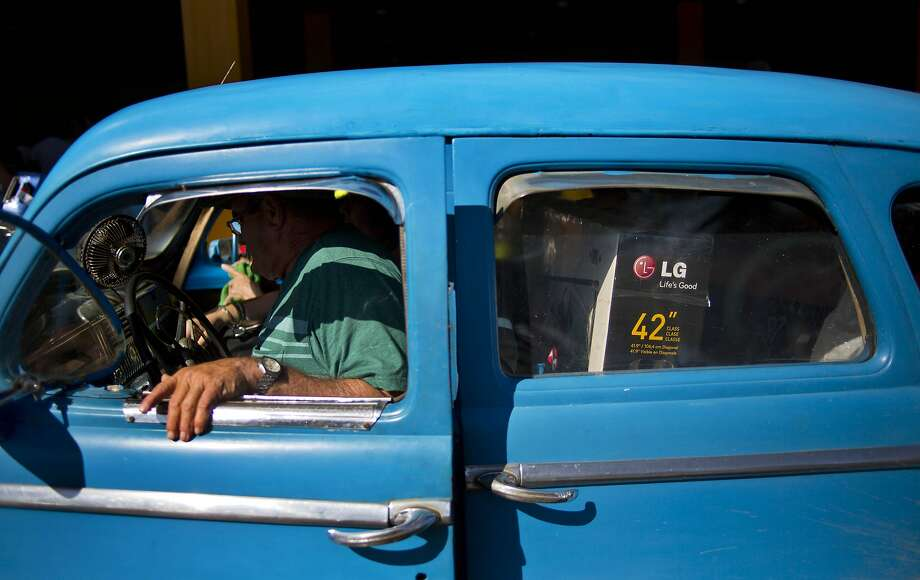 The driver of a private taxi cab closes the door of his car, with the back seat loaded with his client's TV brought from the U.S., as he leaves the Jose Marti International Airport in Havana, Cuba, Monday, Sept. 1, 2014. Cubans braced Monday for a clampdown on the flow of car tires, flat-screen televisions, blue jeans and shampoo in the bags of travelers who haul eye-popping amounts of foreign-bought merchandise to an island where consumer goods are frequently shoddy, scarce and expensive.  Photo: Ramon Espinosa, Associated Press