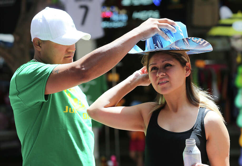 Jorge Linares tries a beer hat on his wife, Juliana, at the Team Beer Hats booth in El Mercado, Monday, Sept. 1, 2014. Long time friends Eric Costilla and Adrian Buitron started making the hats out of beer cartons, gift wrappers and other items over three years ago. Photo: Jerry Lara, San Antonio Express-News / @San Antonio Express-News