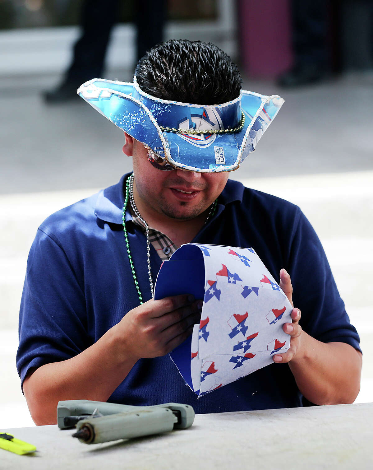 Eric Costilla makes a Texas-themed hat at the Team Beer Hats booth in El Mercado, Monday, Sept. 1, 2014. Costilla and long time friend Adrian Buitron started the company making hats out of beer cartons and giftwraps.