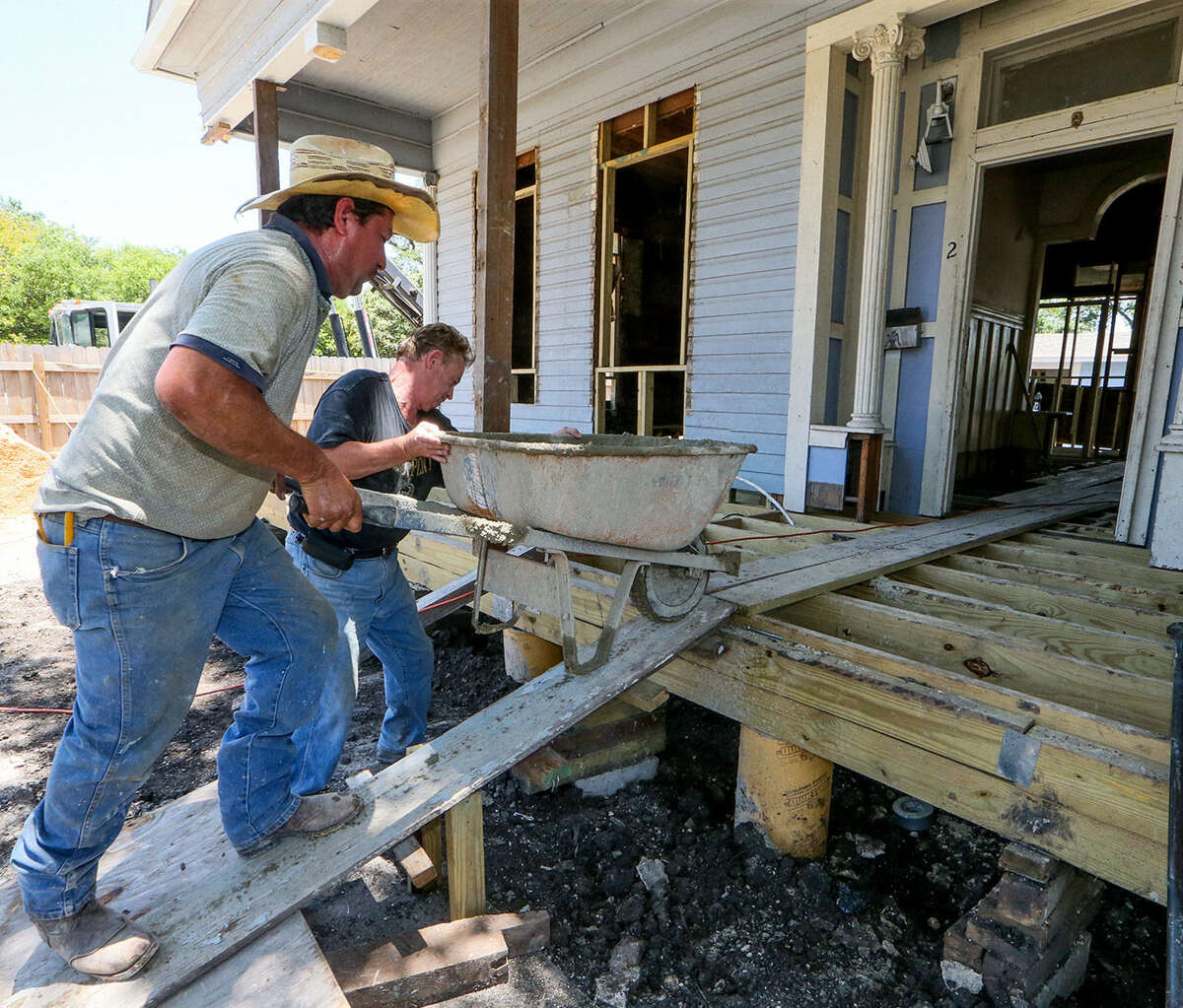 Jim Hogarth (right) helps Carmello Pas push a wheelbarrow of concrete into a Victorian style house he is rebuilding at 506 Dakota near the Alamodome.