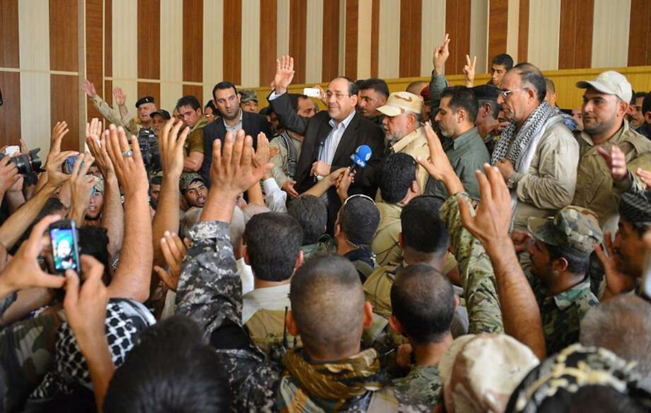 Prime Minister Nouri al-Maliki (back center) makes a surprise visit to Amirli after the town's siege ended. Photo: Associated Press