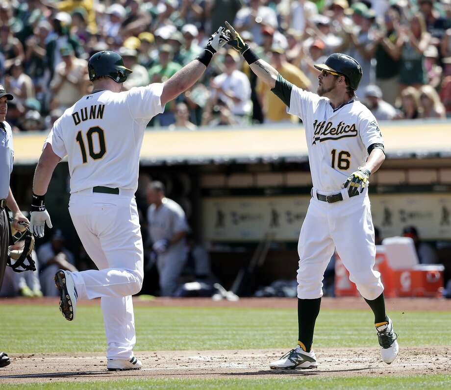 Adam Dunn celebrates his first-inning homer with Josh Reddick. Dunn had two hits in his first game for Oakland. Photo: Marcio Jose Sanchez, Associated Press