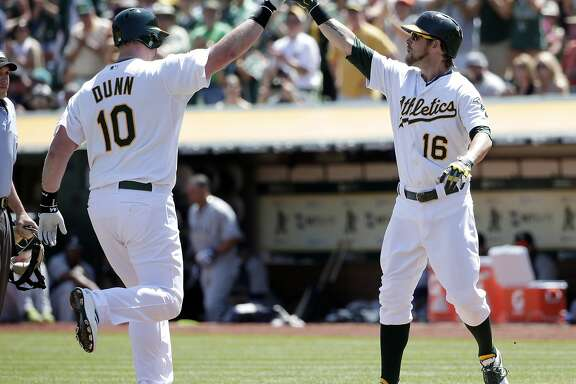Oakland Athletics' Adam Dunn, left, celebrates his two-run home run with teammate Josh Reddick during the first inning of a baseball game on Monday, Sept. 1, 2014, in Oakland, Calif. (AP Photo/Marcio Jose Sanchez)