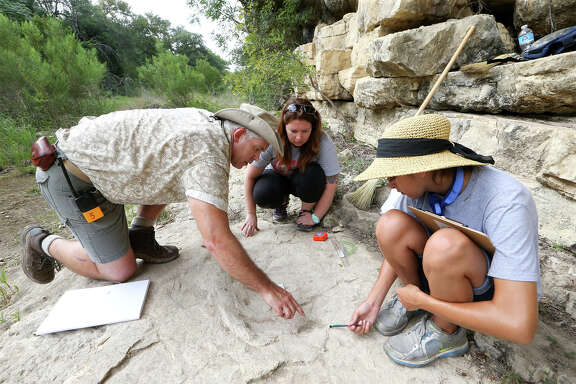 Dr. Thomas Adams assists volunteers Diana Price and Jennifer Shaeffer in measuring the rear foot of a track believed to have been made by a Sauroposei- don and discovered at Government Canyon State Natural Area.