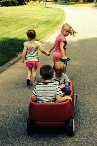 Natalie Miller pulls a wagon as she and her friends head for the park in Clifton Park. To the left is June Houser, sitting in the wagon facing the camera is Levi Houser and boy with his back to the camera is Alex Miller. They are cousins ? two sets of brother and sister. ( Gina Miller )