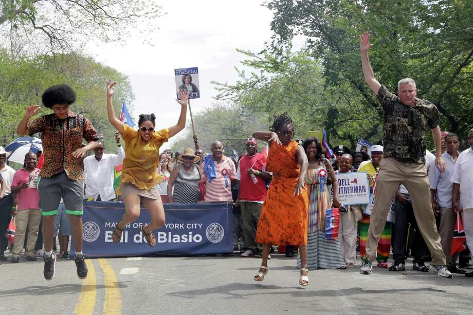 "New York Mayor Bill de Blasio, right, and his children, Dante, left, and Chiara, second left, and wife, Chirlane McCray, do the ""Smackdown"" dance move as they march in the West Indian Day Parade, Monday, Sept. 1, 2014, in the Brooklyn borough of New York.  Photo: Mark Lennihan, Associated Press / AP"