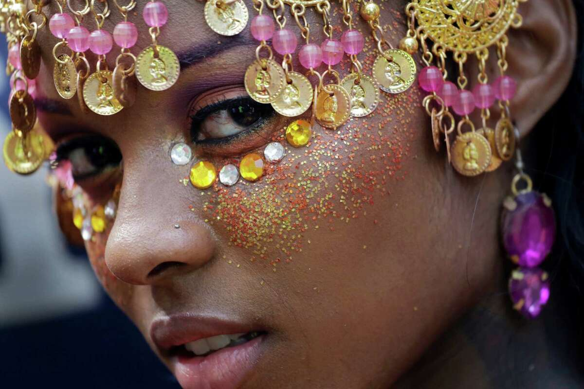A dancer poses for a photograph during the West Indian Day Parade, Monday, Sept. 1, 2014 in the Brooklyn borough of New York. The annual parade draws about 1 million people along its 2-mile-long route.