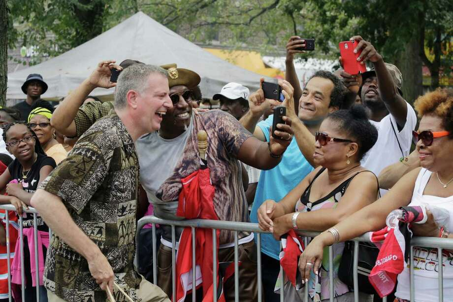 New York Mayor Bill de Blasio, left, poses for photos with revelers at the West Indian Day Parade, Monday, Sept. 1, 2014 in the Brooklyn borough of New York.  Photo: Mark Lennihan, Associated Press / AP